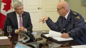 Canadian Prime Minister Stephen Harper is briefed by Royal Canadian Mounted Police (RCMP) commissioner Bob Paulson following a shooting incident on Parliament Hill in Ottawa in this handout photo